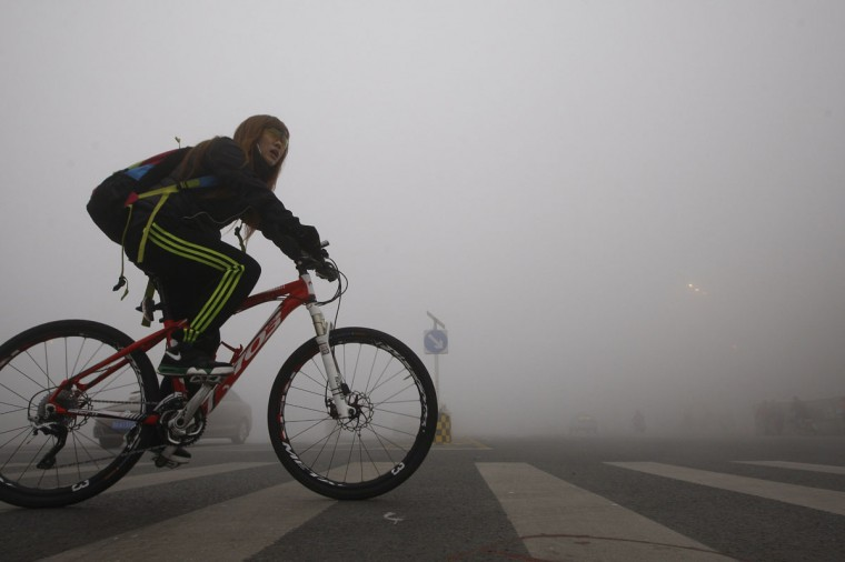 A girl cycles on a street under heavy smog in Harbin. (AFP/Getty Images)