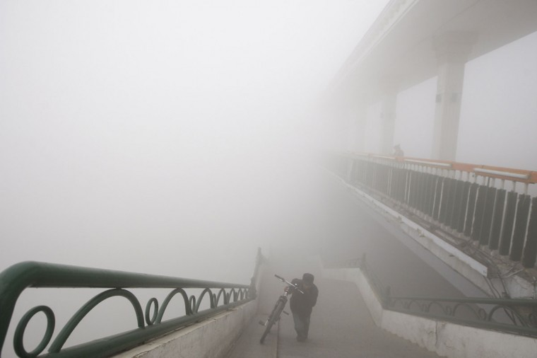 A man pushes his bike onto a bridge under heavy smog in Harbin. (AFP/Getty Images)