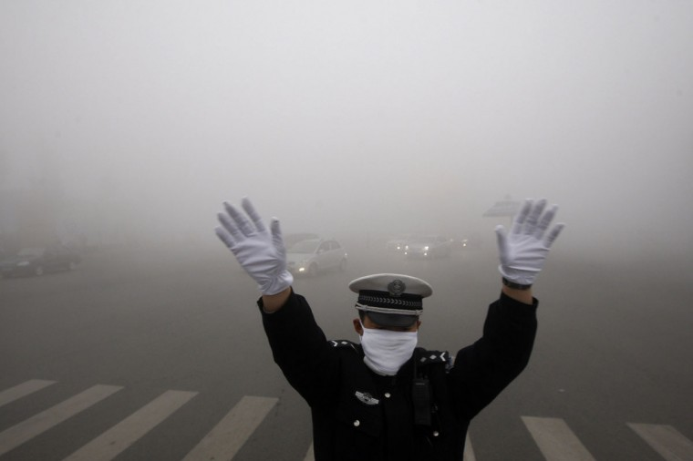 A policeman gestures as he works on a street in heavy smog in Harbin. (AFP/Getty Images)