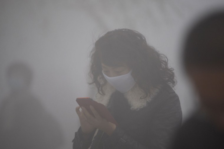A woman wearing a mask uses her mobile phone in the smog in Harbin. (AFP/Getty Images)