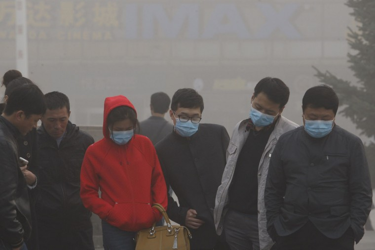 Residents with masks on their faces are seen under heavy smog in Harbin. (AFP/Getty Images)