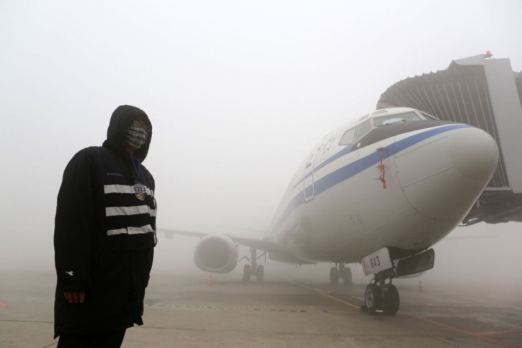 A man stands next to an airplane under heavy smog in Harbin. (AFP/Getty Images)