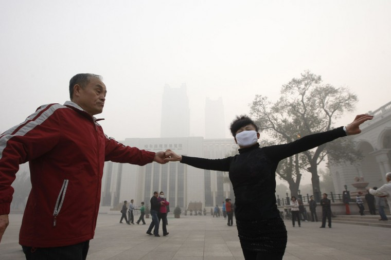 Local residents dance on a square under heavy smog in Harbin. (AFP/Getty Images)