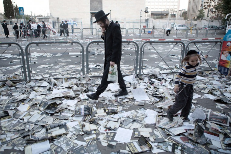 An orthodox Jewish man walks at a street covered with election campaign leaflets in Jerusalem on the eve of Israel's municipal elections. (MENAHEM KAHANA / AFP/Getty Images)