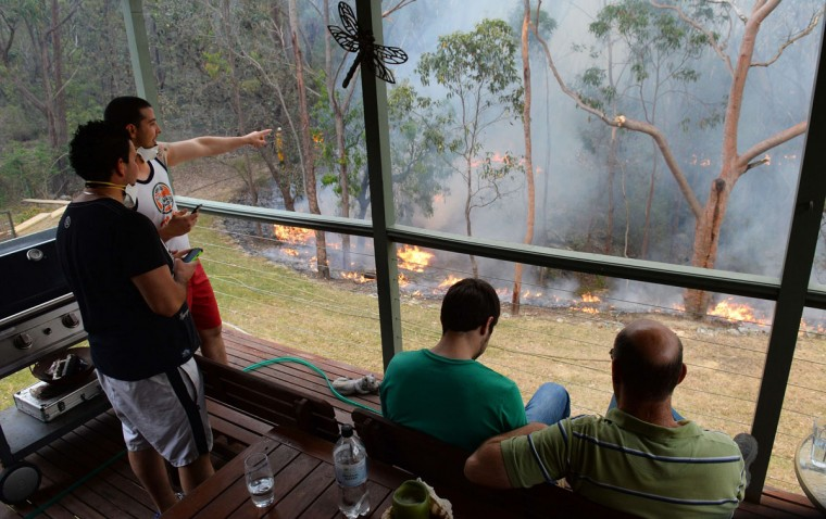 Local residents watch the containment of fires from the balcony on a house at Faulconbridge in the Blue Mountains on October 22, 2013. Firefighters on October 22 deliberately merged two major blazes in southeastern Australia in a desperate battle to manage the advancing infernos as weather conditions worsen. (William West/AFP/Getty Images)