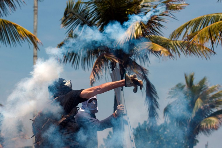 Activists protest in front of the hotel where Brazil's National Petroleum Agency auctions drilling rights to one of the world's largest offshore oil discoveries in Barra de Tijuca, Rio de Janeiro, Brazil. (CHRISTOPHE SIMON / AFP/Getty Images)