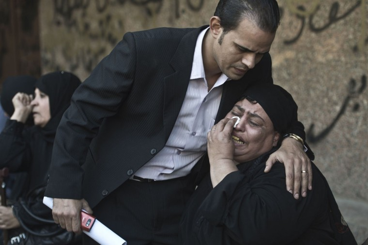 An Egyptian relative of one of the victims of a shooting spree targeting a wedding at a Cairo Coptic Church is comforted as she mourns at a morgue in the capital. (KHALED DESOUKI / AFP/Getty Images)