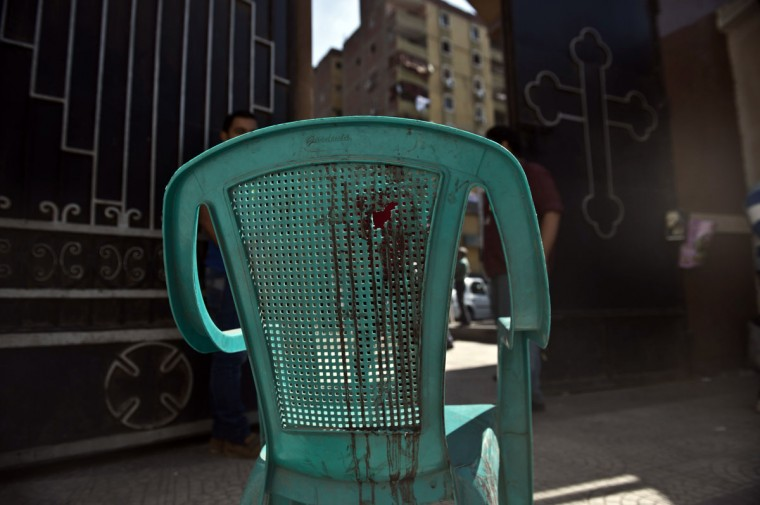 A chair with a hole and blood stains is seen at the entrance of the Virgin Mary Coptic Christian Church in Cairo after gunmen on a motorbike killed several people, including an eight-year-old girl, the previous night in a shooting attack on a group standing outside the church. (KHALED DESOUKI / AFP/Getty Images)