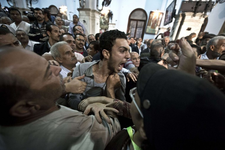 An Egyptian Coptic man reacts during the funeral service of four victims, gunned down as they attended a wedding the previous evening at the Virgin Mary Coptic Christian church in Cairo's working class neighborhood of Al-Warrak. (KHALED DESOUKI / AFP/Getty Images)
