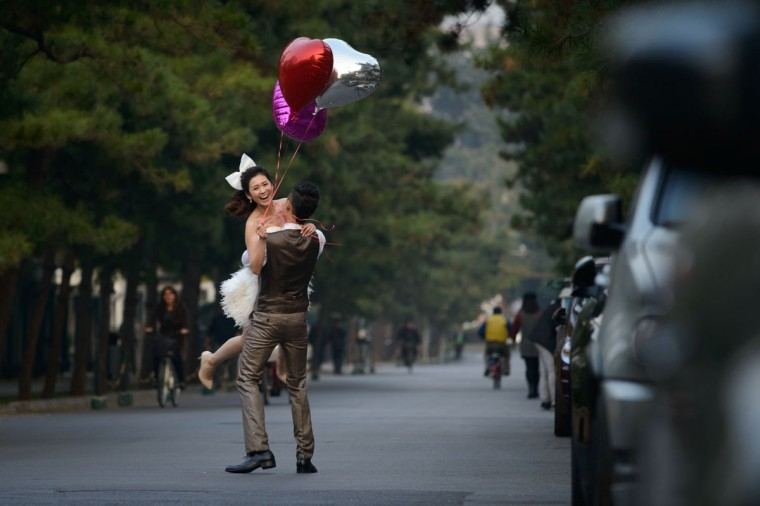 A woman wearing a wedding dress and holding heart-shaped balloons is lifted by a man on a street in Beijing. China's gross domestic product expanded 7.8 percent year-on-year in July-September, data showed, snapping two quarters of slowing growth in world's second-largest economy. (Ed Jones / AFP/Getty Images)