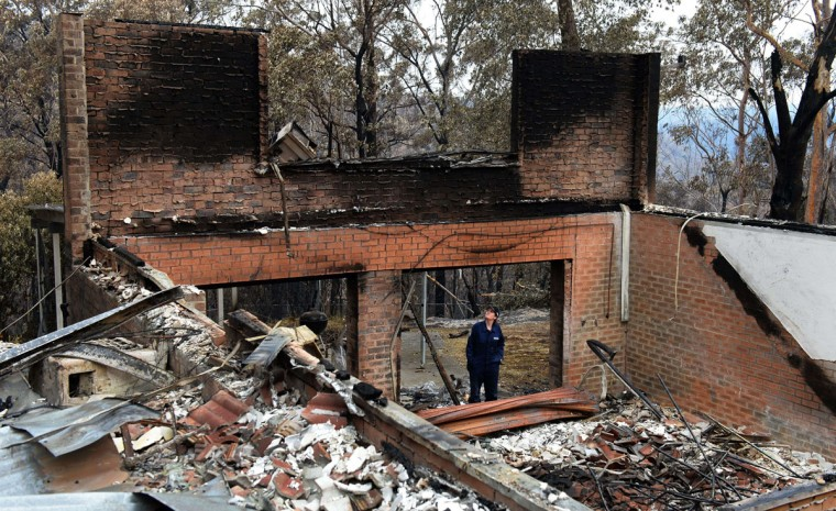 Policewoman Tegan Mobbs looks at the remains of her home in Yellow Rock in the Blue Mountains on October 22, 2013, after it was destroyed in a firestorm which tore through the area. The granite slabs that were once a kitchen bench were still warm after five days and a chimneystack and fireplace are all that remain upright in the ruins of what was once a five-bedroom home on a picturesque five-acre bush block in Yellow Rock, west of Sydney. (William West/AFP/Getty Images)