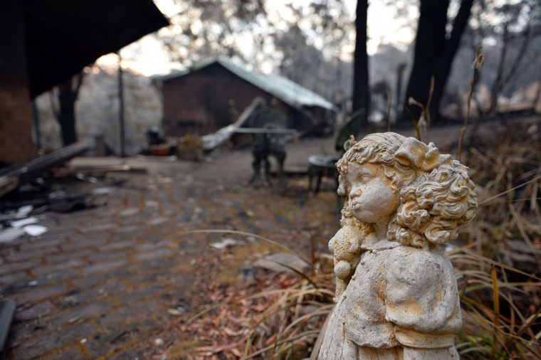 """A statue stands outside a burnt out home in Winmalee in the Blue Mountains on October 22, 2013. Firefighters on October 22 deliberately merged two major blazes in southeastern Australia in a desperate attempt to manage the advancing infernos ahead of weather conditions that authorities warn will be """"as bad as it gets"""". (Saeed Khan/AFP/Getty Images)"""