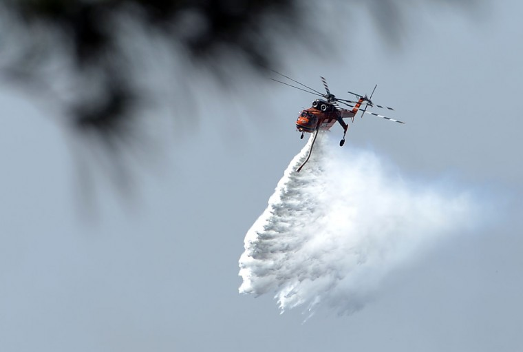 A helicopter drops water to douse bushfires along the Linksview Road near Faulconbridge in the Blue Mountains on October 23, 2013. Firefighters in Australia battled hot, dry winds and soaring temperatures on October 23 as new blazes began breaking out in a week-long bushfire disaster that shows no signs of easing. (Saeed Khan/AFP/Getty Images)