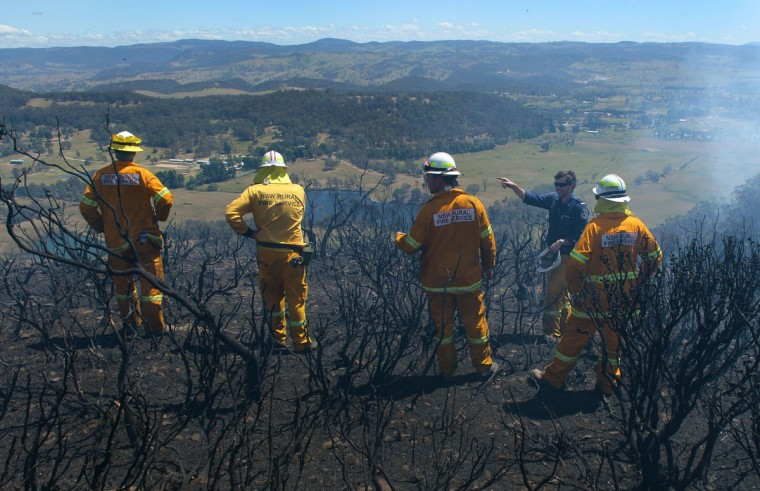 Volunteer firefighters look out over the escarpment from the Mt. York fire area near Mt. Victoria in the Blue Mountains, roughly 150 kilometers west of Sydney, on October 23, 2013. As the crisis entered its seventh day, at least 65 fires were raging across the state of New South Wales with 18 of them uncontained and warnings again issued for people to leave their homes or be extra vigilant. (William West/AFP/Getty Images)