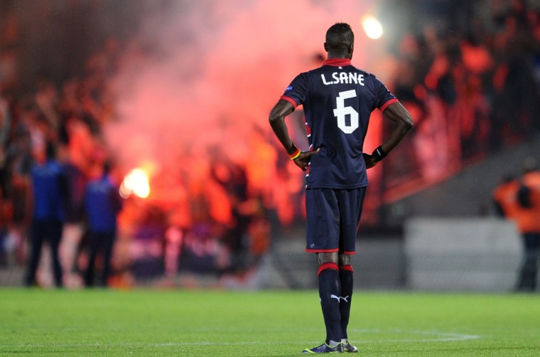 Bordeaux' defender Ludovic Sane stands in the pitch as fans light flares during the UEFA Europa League group F football match between Bordeaux and APOEL Nicosia at the Chaban Delmas Stadium in Bordeaux on October 24, 2013. (Nicolas Tucat/AFP)