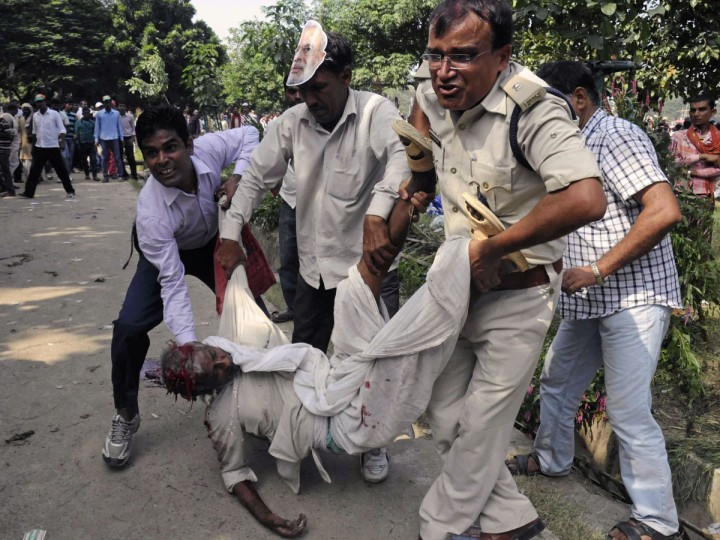 An Indian police deputy superintendent and other bystanders assist an injured man when a series of bombs went off during an opposition Bharatiya Janata Party rally in Patna. A series of crude bombs killed five people in an eastern Indian city, shortly before opposition party leader Narendra Modi was due to hold a campaign rally, police said. (STRSTRDEL / AFP/Getty Images)