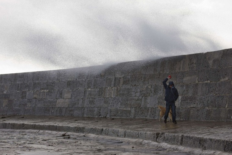 A man walks his dog along a sea wall in Lyme Regis, southern England on October 27, 2013 as strong winds blow spray over the sea wall. Britain was braced on October 27 for its worst storm in a decade, with heavy rain and winds of more than 80 miles an hour set to batter the south of the country. (Justin Tallis/AFP/Getty Images)