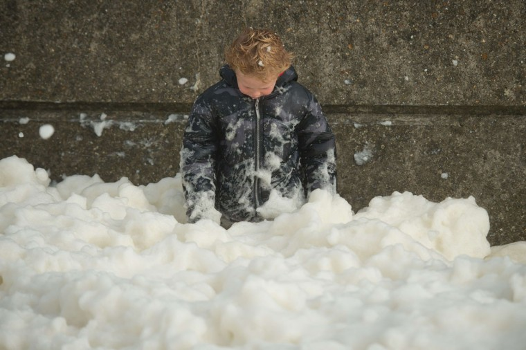 A boy plays in the foam washed ashore on the Brighton seafront on October 27, 2013 as high winds pick up ahead of an expected storm. Britain was braced on October 27 for its worst storm in a decade, with heavy rain and winds of more than 80 miles an hour set to batter the south of the country. (Leon Neal/AFP/Getty Images)