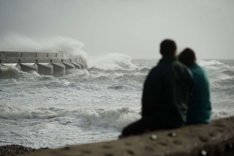 People sit and watch as large waves crash against the walls of Brighton Marina, southern England on October 27, 2013 as high winds pick up ahead of an expected storm. Britain was braced on October 27 for its worst storm in a decade, with heavy rain and winds of more than 80 miles an hour set to batter the south of the country. (Leon Neal/AFP/Getty Images)