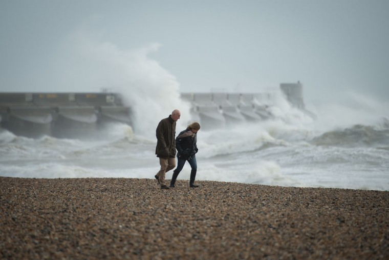 People take a walk along the pebble beach as large waves crash against the walls of Brighton Marina in the background in Brighton, southern England on October 27, 2013. Britain was braced on October 27 for its worst storm in a decade, with heavy rain and winds of more than 80 miles (130 kilometers) an hour set to batter the south of the country. (Leon Neal/AFP/Getty Images)