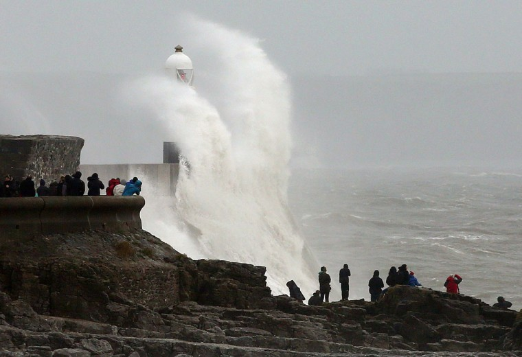 People watch as large waves break against barriers at the harbor in Porthcawl, south Wales on October 27, 2013 ahead of the arrival of a predicted storm. Britain was braced on October 27 for its worst storm in a decade, with heavy rain and winds of more than 80 miles (130 kilometers) an hour set to batter the south of the country. (Geoff Caddick/AFP/Getty Images)