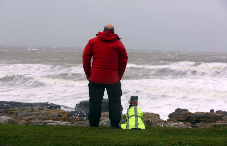 A man and his dog stand watching as waves roll in at the beach in Porthcawl, south Wales on October 27, 2013 ahead of the arrival of a predicted storm. Britain was braced on October 27 for its worst storm in a decade, with heavy rain and winds of more than 80 miles (130 kilometers) an hour set to batter the south of the country. (Geoff Caddick/AFP/Getty Images)