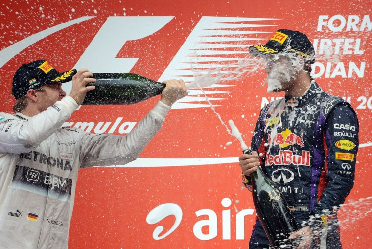 Red Bull driver Sebastian Vettel of Germany (right) celebrates his victory with Mercedes driver Nico Rosberg of Germany on the podium at the Formula One Indian Grand Prix 2013 at the Buddh International circuit in Greater Noida. (PRAKASH SINGH / AFP/Getty Images)