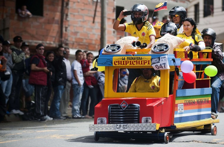 """Participants descend a hill in a homemade """"Chiva"""" -- traditional bus -- car during the XXIV Car Festival in Medellin, Colombia. (RAUL ARBOLEDA / AFP/Getty Images)"""
