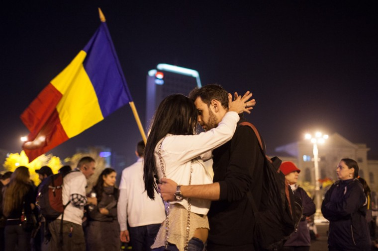 Two protesters share a moment of intimacy outside the Romanian government headquarters during a rally in Bucharest against the Rosia Montana Gold Corporation (RMGC), a Canadian gold mine project using cyanide, and against shale gas exploitation. (ANDREI PUNGOVSCHI / AFP/Getty Images)