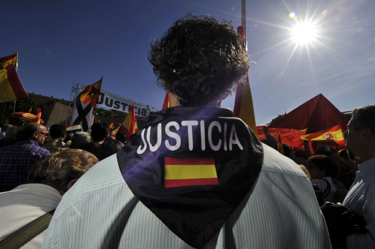 """A man with a scarf with a Spanish flag and reading """"Justice"""" as he gathers with thousands of Spaniards at Plaza de Colon to answer a call by Association of Victims of Terrorism (AVT) to protest against a European court ruling that could lead to the release of dozens of militants. (GERARD JULIEN / AFP/Getty Images)"""