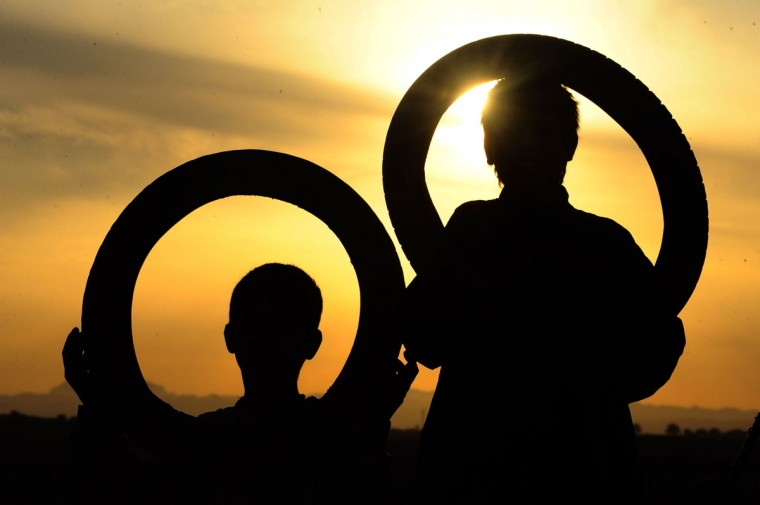 Young Afghan children pose with tires on the outskirts of Herat. Economic development is considered a vital weapon to stop the country from sinking back into civil war and to stem Islamist extremism after 100,000 international combat troops pull out next year. (Aref Karimi / AFP/Getty Images)