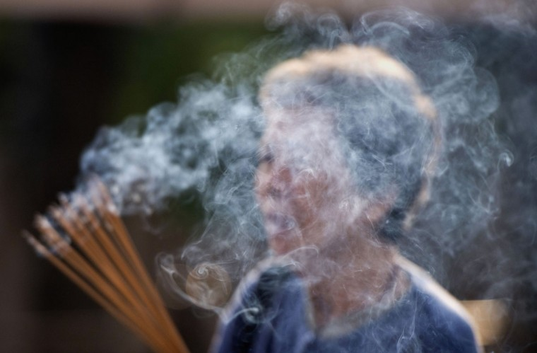 A woman prays holding incense sticks at the Wong Tai Sin temple in Hong Kong. The Taoist temple is a major tourist attraction and center for worship in Hong Kong. (Alex Ogle / AFP/Getty Images)