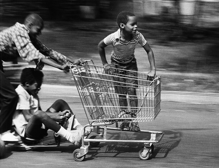 A shopping cart becomes a go-cart for LeRoy Simon, 13, who pushes off with Jack Burris, 15 (seated), to provide steering and braking and Derek Brown, 9, along for the ride in August 1981. (Ellis Malashuk/Baltimore Sun)