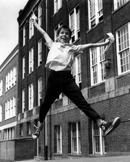 Raymond McGrew, 13, leaps with joy outside Public School No. 47 at Fleet Street and Linwood Avenue in Baltimore in June 1963, as school is out and his report card shows passing grades. (Ellis Malashuk/Baltimore Sun)