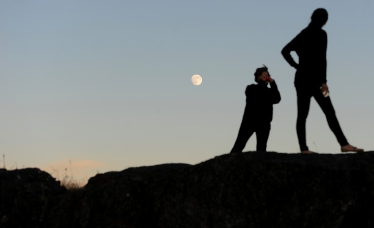 Visitors to a park overlooking Victoria, British Columbia document their trip as the moon rises. (Kim Hairston/Baltimore Sun)