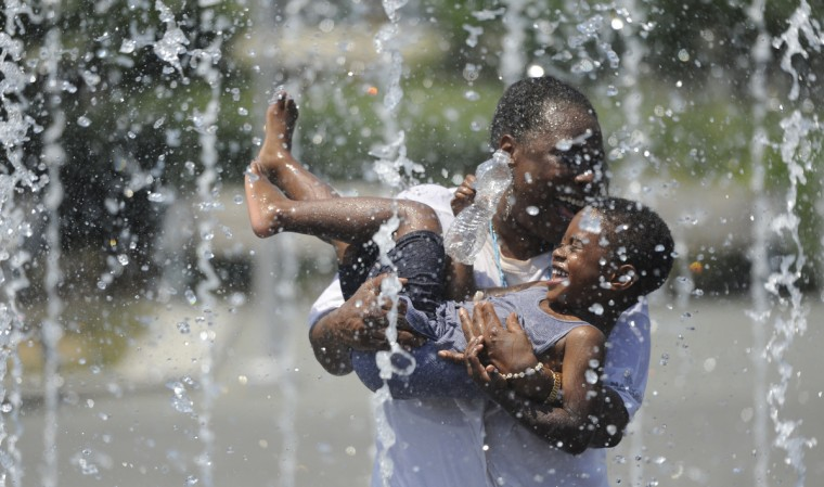 Lisa Mills and her grandson Donte Gardner, 3, both of Baltimore, play in the Sondheim Fountain at the Inner Harbor in July 2012. (Barbara Haddock Taylor/Baltimore Sun)