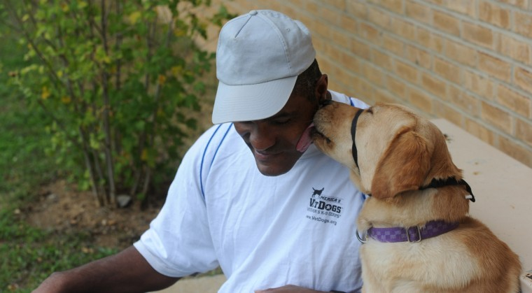 Terry Dorsey, 50, gets a lick from Delta, a labrador he is working with to be a service dog. Dorsey is among incarcerated veterans and other prisoners training service dogs for wounded service people at Maryland Correctional Institution-Hagerstown. Delta will be graduating and leaving the prison. (Kim Hairston/Baltimore Sun)