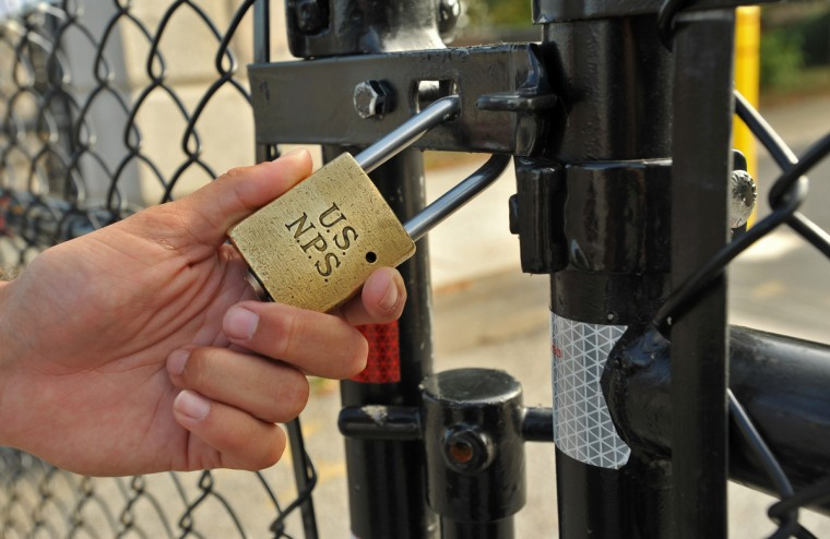 Park Ranger Tyler Mink, who has worked at Fort McHenry for 5 years, and volunteered at the Fort for 5 years before being hired, locks the gate after leaving Tuesday morning. (Amy Davis/Baltimore Sun)