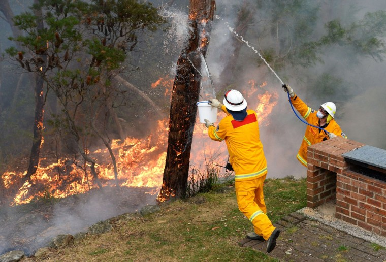 Firefighters work to contain fires from a resident's backyard at Faulconbridge in the Blue Mountains on October 22, 2013. Firefighters on October 22 deliberately merged two major blazes in southeastern Australia in a desperate battle to manage the advancing infernos as weather conditions worsen. (William West/AFP/Getty Images)
