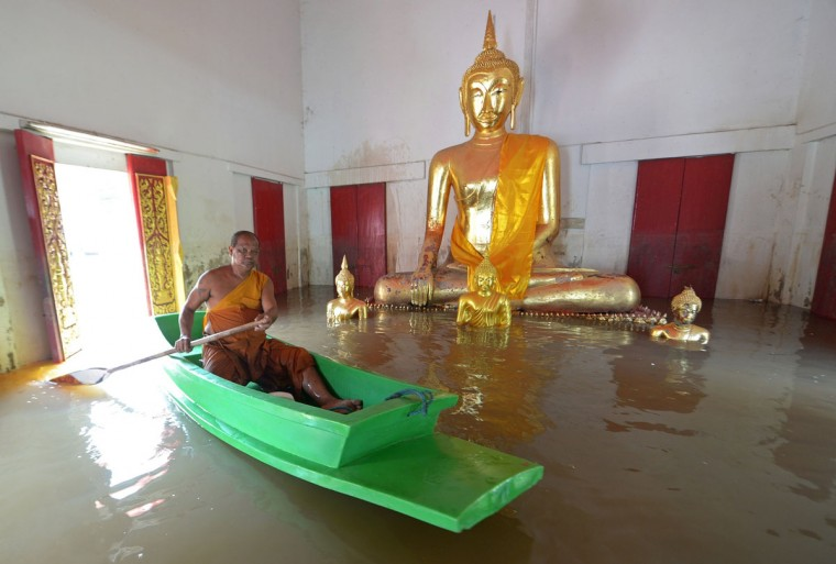 A buddhist monk paddles a boat past a buddha statue at a temple in Ayutthaya province, north of Bangkok. The Disaster Prevention and Mitigation Department reported that 25 provinces in Thailand are still flooded and 27 people have died due to the flood. (PORNCHAI KITTIWONGSAKUL / AFP/Getty Images)