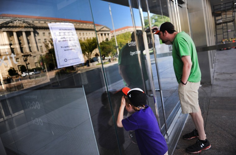 Tourists find the doors to the Museum of American History closed due to the federal government shutdown, Tuesday, Oct. 1, 2013 in Washington, D.C. President Barack Obama declared the government had officially run out of money when the fiscal year expired at 12:01 a.m. Tuesday. (Olivier Douliery/Abaca Press/MCT)