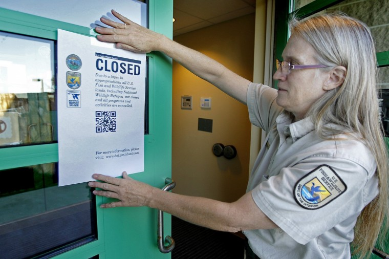 "Jeanne Holler, Deputy Refuge Manager at the Minnesota Valley Wildlife Center hangs a ""Closed"" sign outside the center in Bloomington, Minnesota, early Tuesday, Oct. 1, 2013. President Barack Obama declared the government had officially run out of money when the fiscal year expired at 12:01 a.m. Tuesday. (Elizabeth Flores/Minneapolis Star Tribune/MCT)"