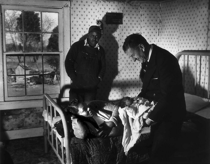 Under the watchful eye of the new parents, an unidentified country doctor gets acquainted with a young patient during a house call on the Eastern Shore in May 1952. (Hans Marx/Baltimore Sun)