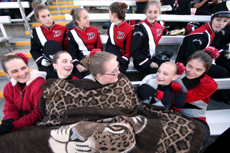 Dulaney High School Marching Band's Haley Szoke, left, 17, Danielle Szoke, 17, Barbara Bafford, 17, Rebecca Friedel, 17, and Nicole Konstant, right, 17, try to stay warm before the start. (Jen Rynda/BSMG)