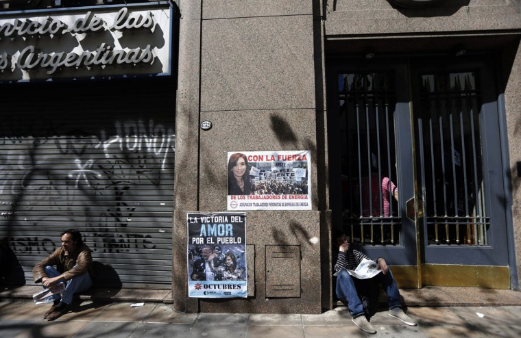 "Supporters of Argentina's President Cristina Fernandez wait next to posters with her image outside the hospital where she had surgery in Buenos Aires, October 8, 2013. Fernandez had surgery on Tuesday to remove blood from the surface of her brain, sidelining her three weeks ahead of a key mid-term election and at the apex of a rancorous court battle with the nation's ""holdout"" creditors. (Marcos Brindicci/Reuters)"