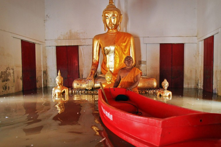 A Buddhist monk pushes a small plastic boat as he shows his flooded temple to reporters at Bang Ban district in Ayutthaya province. More than 2 million people have been affected by flooding in Thailand, officials said on Monday, while authorities warned that more heavy rains could inundate the country's northeast but offered assurances that there would be no repeat of 2011 when floodwaters reached central industrial areas and near Bangkok. (Chaiwat Subprasom/Reuters)