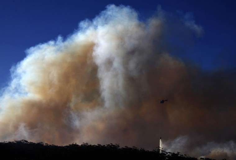 A helicopter drops water on a bushfire approaching homes near the Blue Mountains suburb of Blackheath, located around 43 miles west of Sydney, October 23, 2013. A state of emergency has been declared in the Australian state of New South Wales, as bushfires continue to burn west of Sydney, and weather conditions expected to worsen over the coming days. Around 60 fires are still burning across the state. (David Gray/Reuters)