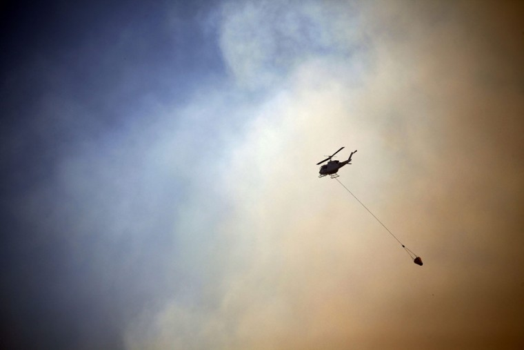 A helicopter drops water on a fire approaching homes near the Blue Mountains suburb of Blackheath, located around 43 miles west of Sydney, October 23, 2013. A state of emergency has been declared in the Australian state of New South Wales, as bushfires continue to burn west of Sydney and weather conditions expected to worsen over the coming days. Around 60 fires are still burning across the state. (David Gray/Reuters)