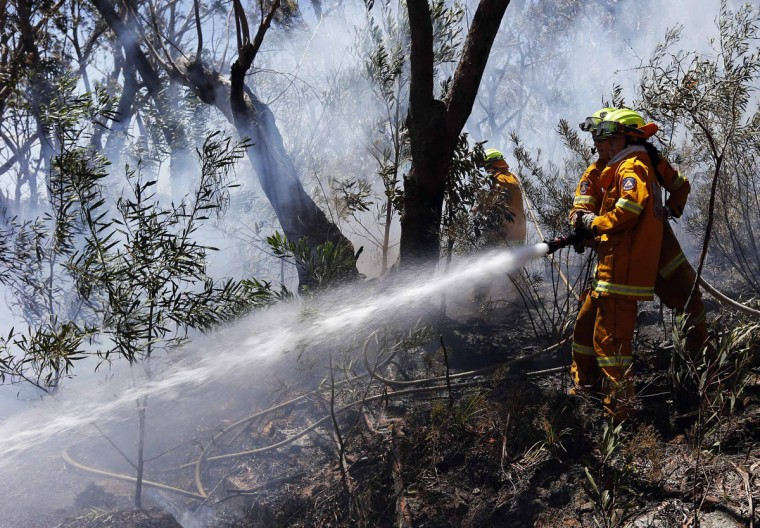 Rural Fire Service (RFS) firefighters tries to extinguish a small fire approaching homes near the Blue Mountains suburb of Blackheath, located around 43 miles west of Sydney, October 23, 2013. A state of emergency has been declared in the Australian state of New South Wales, as bushfires continue to burn west of Sydney and weather conditions expected to worsen over the coming days. Around 60 fires are still burning across the state. (Reuters Photo)