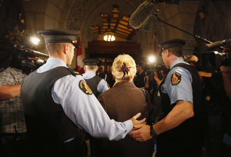 Senator Pamela Wallin is escorted by security into the Senate on Parliament Hill in Ottawa October 24, 2013. The Senate is debating whether to suspend senators Wallin, Mike Duffy and Patrick Brazeau without pay. (Chris Wattie/Reuters)